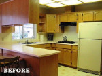 A kitchen with a stove and a refrigerator before remodel
