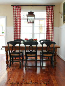 A dining room table with red and white checked curtains