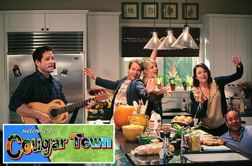 cast of Cougar Town TV show in Jules\'s kitchen with logo inset