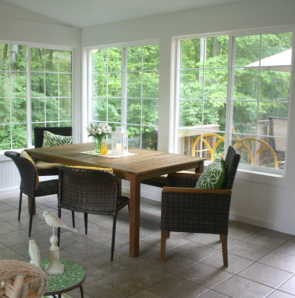 A dining room table in front of a window in sunroom