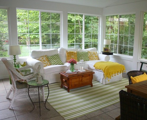 large sunroom with Ektorp sofa from IKEA and green and white stripe rug
