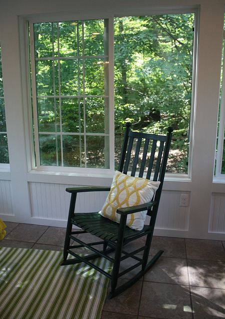 green rocking chair in the sunroom