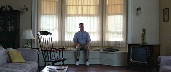 Forrest Gump sits on window seat in bay window of house