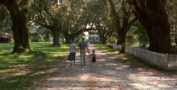 Jenny, Forrest and their son walk down the lane to the house