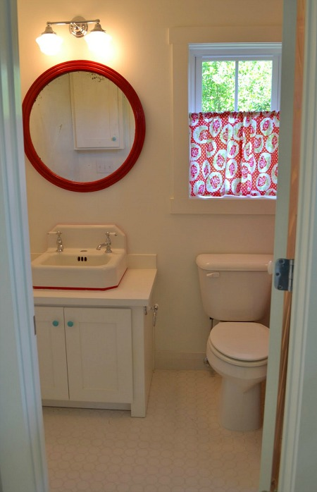 small bathroom with round red mirror over sink