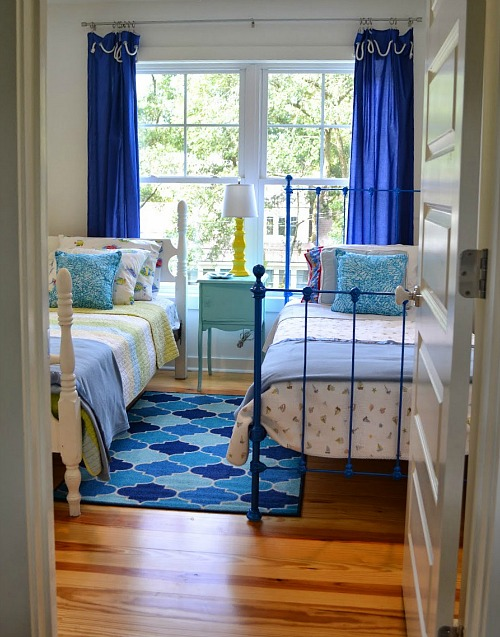 kid\'s bedroom with two twin beds and blue curtains