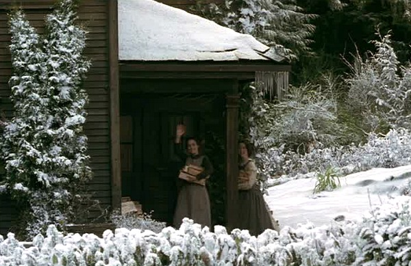 two sisters wave from back of a house covered in snow in Little Women