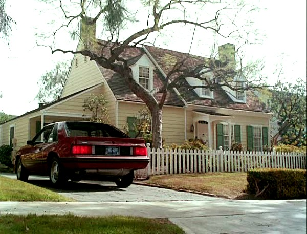 car pulling into driveway beside Cape Cod house from Mr. Mom movie