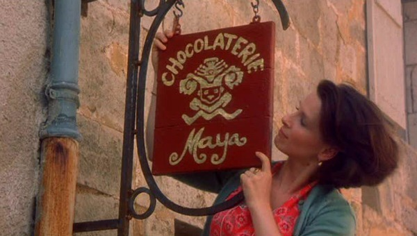 hanging a sign over the door that says Chocolaterie Maya