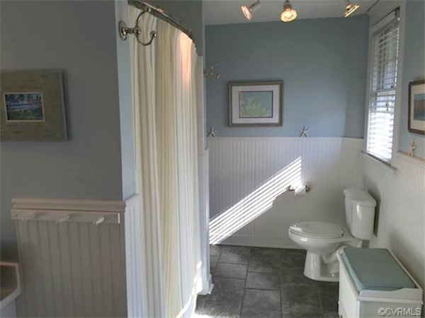 A bathroom with shower curtain and toilet