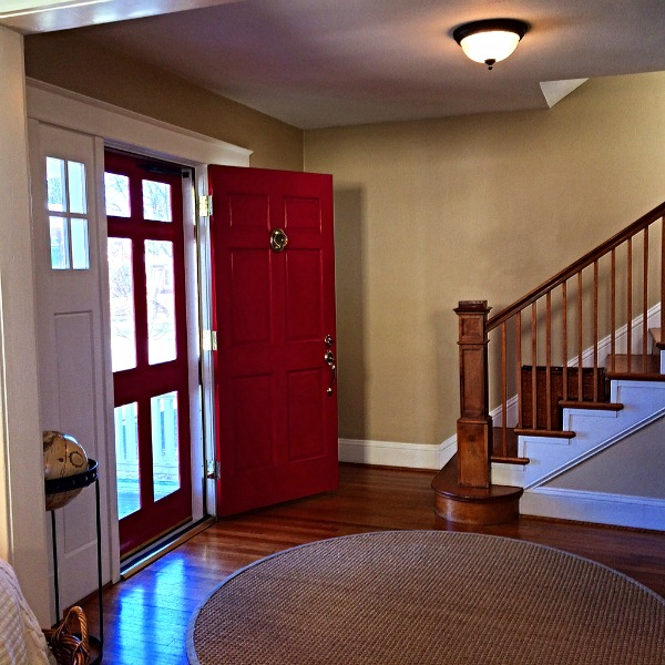 red front door open to entry way and staircase