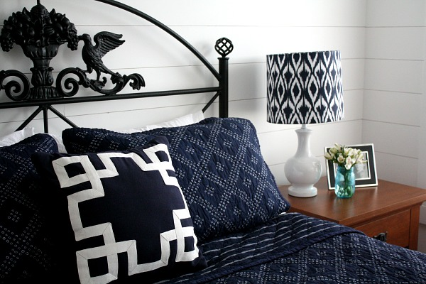 close up of blue and white bedding and black headboard