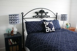 bed with black iron headboard and navy blue quilt