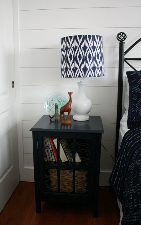navy blue nightstand with blue and white lamp