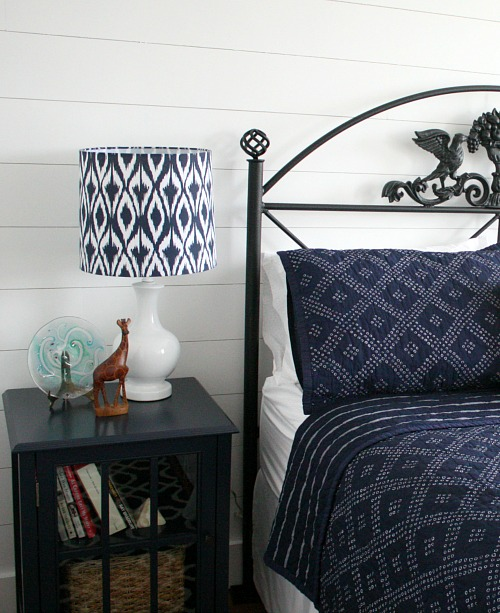close up of black iron headboard and blue nightstand