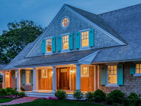 Shingled house with aqua shutters on Cape Cod at night (designed by Polhemus Savery DaSilva Architects)