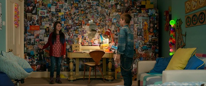 two characters stand in room covered in collage of images