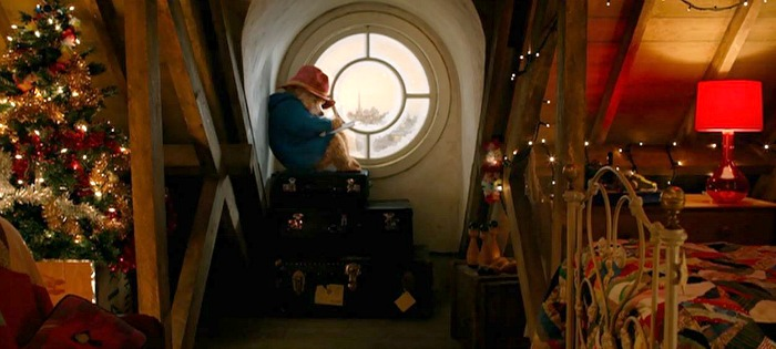 Paddington sits in round window on stack of suitcases