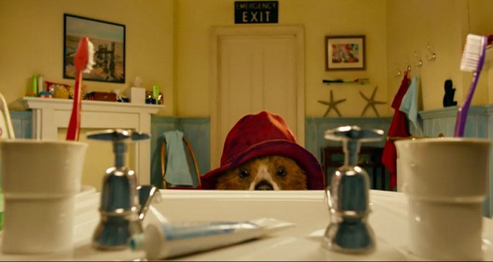 Paddington Bear looks over top of sink at toothpaste tube