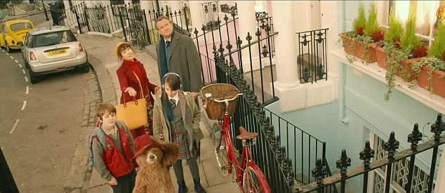 overhead view of characters standing on the street with red bike and Paddington