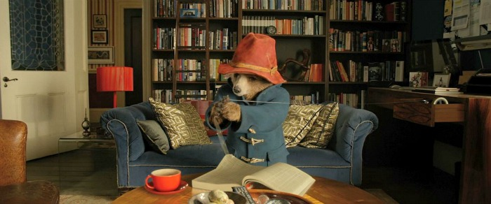 Paddington Bear sits on blue sofa
