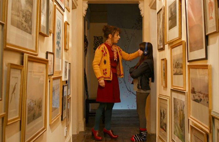 mother and daughter stand in upstairs hallways lined with framed artwork