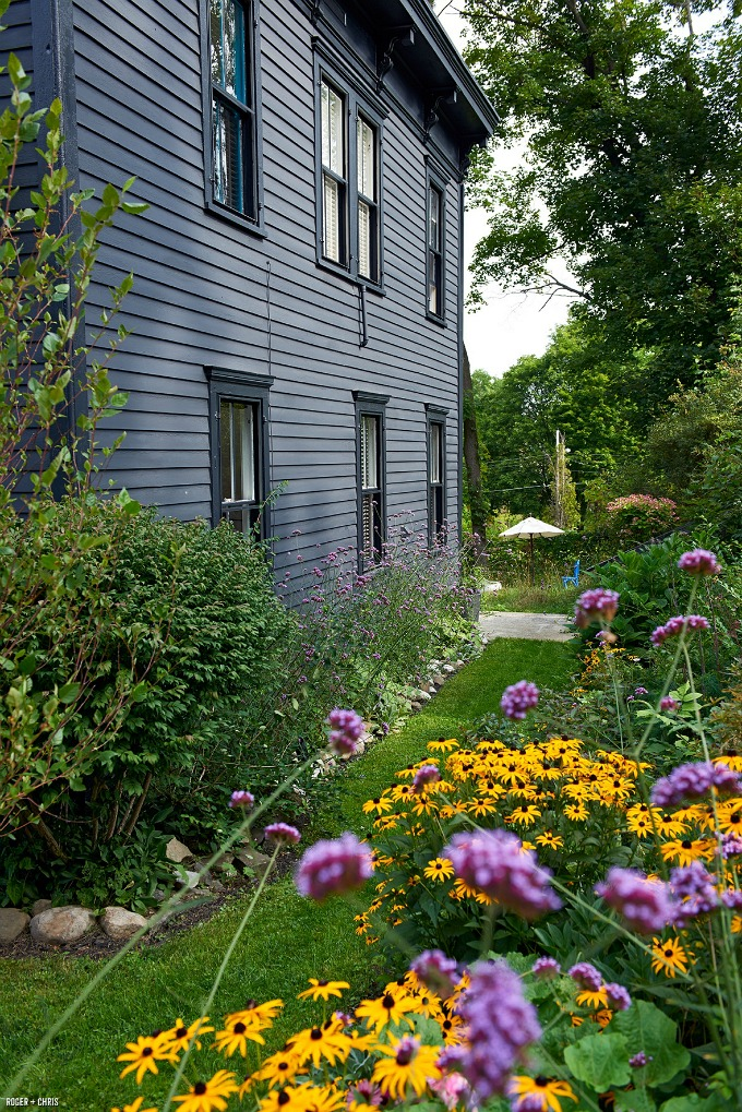 side of black house with cottage garden