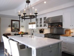 white kitchen with chandelier and marble island