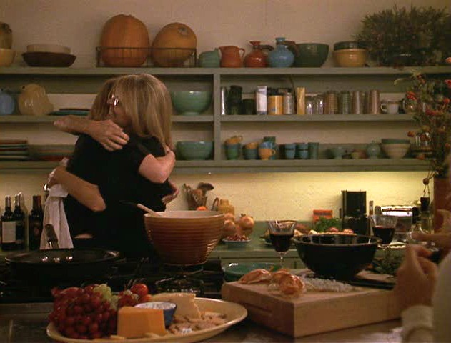 women hugging in kitchen with open shelving