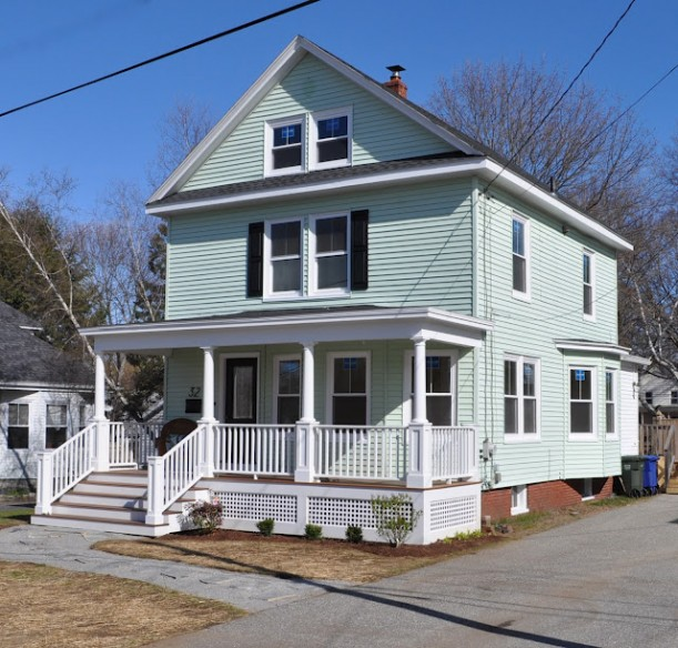 three story traditional home with front porch and black shutters in Maine