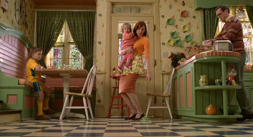 Geena Davis holding little girl in kitchen scene
