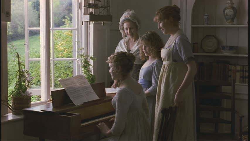 women gathered around a piano in Barton Cottage