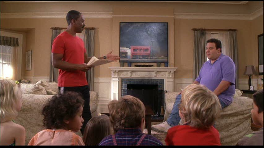 Eddie Murphy standing next to fireplace in living room