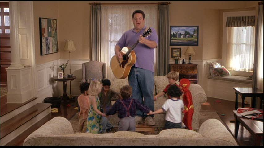 man playing guitar while children hold hands in circle in living room