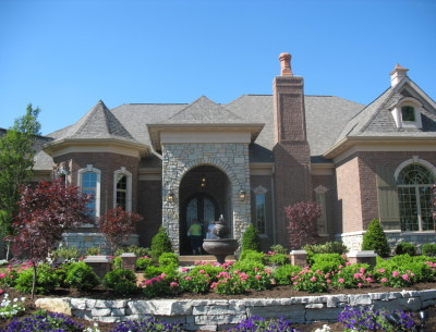 exterior front of large brick house with fountain in front