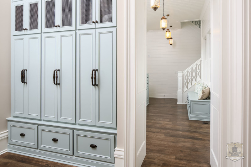 mudroom with built in storage cubbies and doors painted pale blue