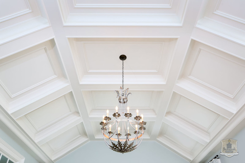 bedroom chandelier hanging from coffered ceiling