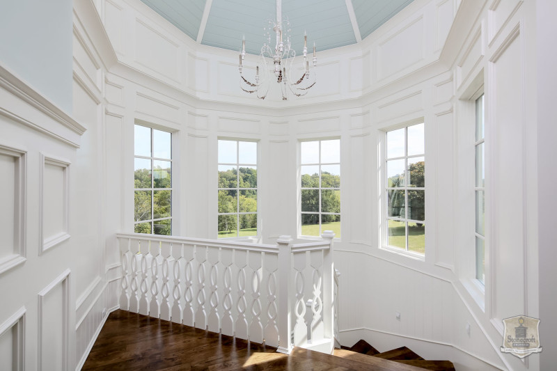 upstairs landing with chandelier and turret of windows