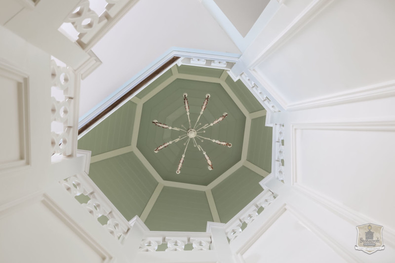looking up staircase to chandelier at the top of the house