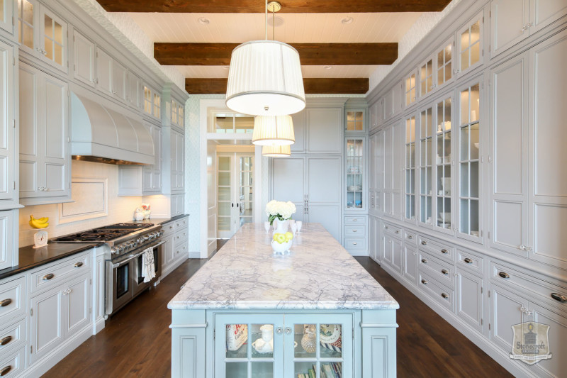 pale blue cabinets in kitchen with long narrow marble island