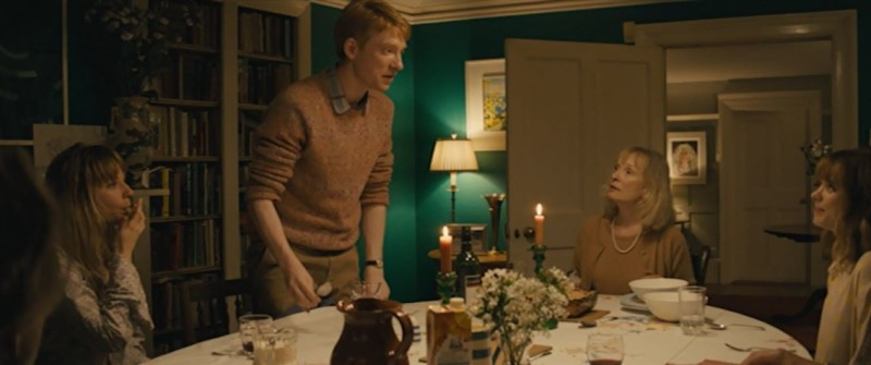 Domhnall Gleeson standing beside dining room table in About Time