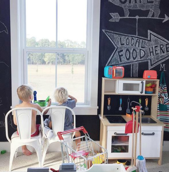 Playroom with black chalkboard wall and kitchen playset