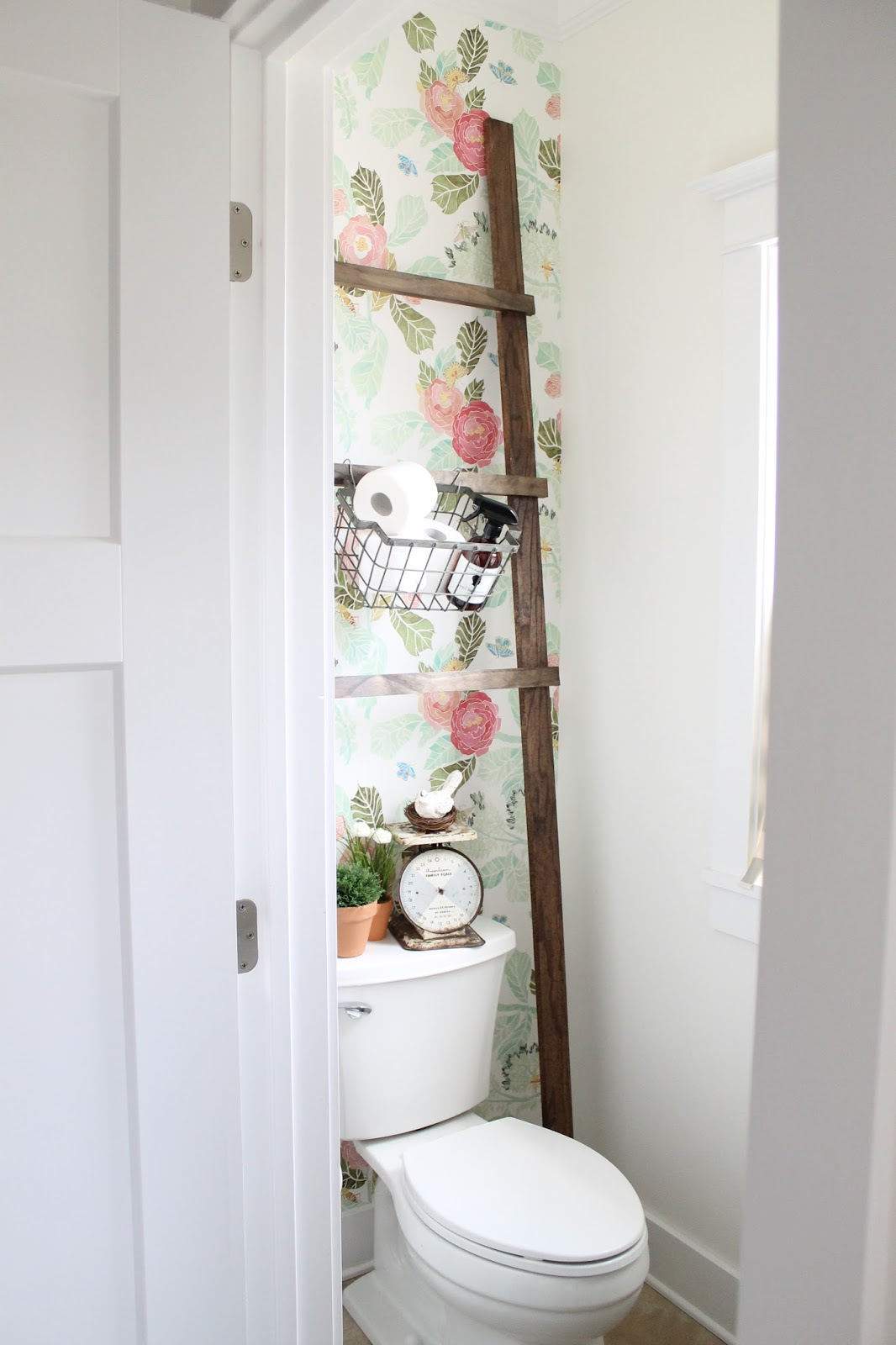 powder room with floral wallpaper and antique ladder