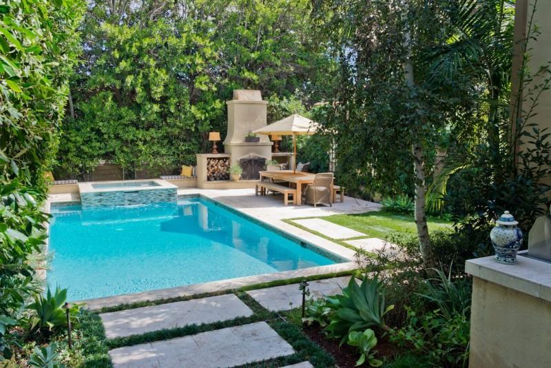 outdoor fireplace beside pool in backyard