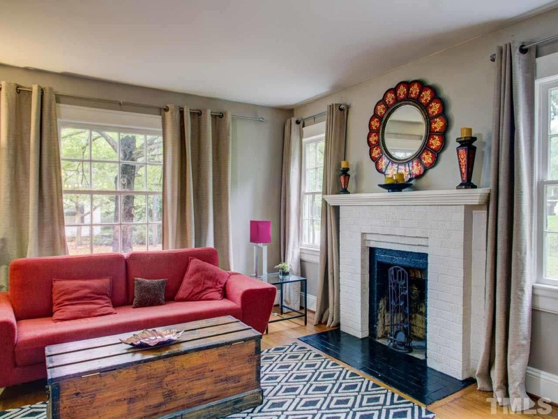 Living room with red sofa and painted brick fireplace