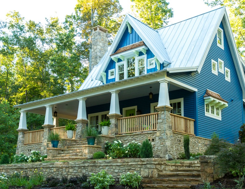 Front exterior of Craftsman style cottage with blue siding and front porch