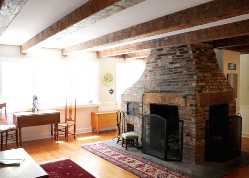 Brick fireplace and beamed ceiling in living room
