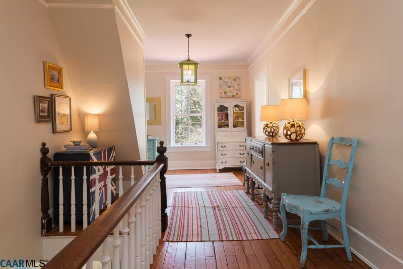 Upstairs landing with striped rug and dresser