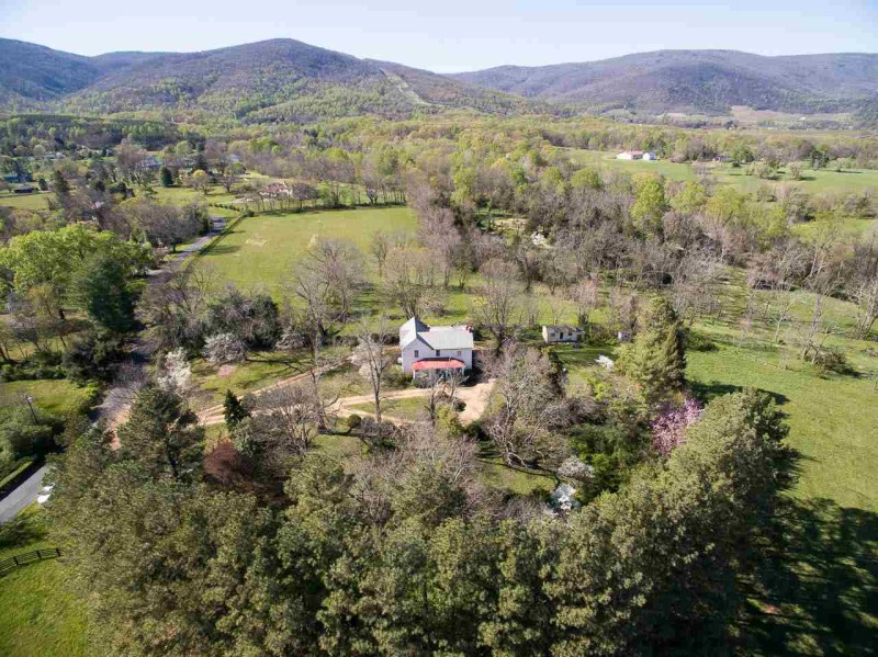 aerial view of white farmhouse and surrounding acreage