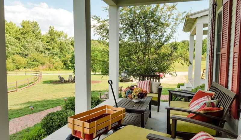 Outdoor seating on front porch of farmhouse